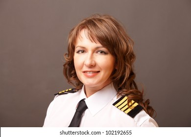 Beautiful woman pilot wearing uniform with epauletes looking ahead