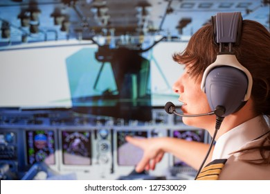 Beautiful woman pilot wearing uniform with epauletes and headset sitting inside airliner and pointing at cockpit during flight.
