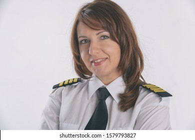 Beautiful woman pilot wearing uniform with epauletes, standing isolated on white background.