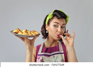 Beautiful woman in pin up style with perfect hair and make up .Expressive facial expressions. Housewife with yummy biscuits.