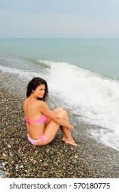Beautiful woman in pink bikini sitting on the sea beach. Woman resting in Batumi, Georgia