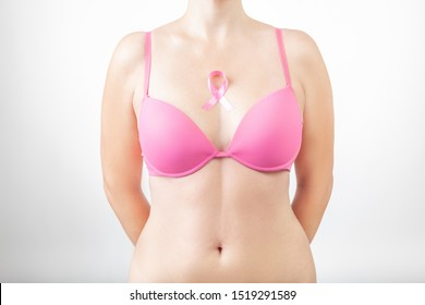 Beautiful woman in pink bra with pink ribbon. Breast cancer symbol