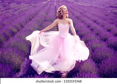 beautiful woman in pink dress dancing in lavender field sunny summer