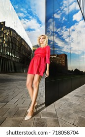 Beautiful woman in pink dress is standing at glass skyscraper wall with city reflection background.