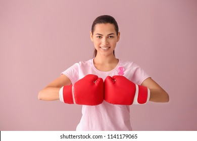 Beautiful woman with pink ribbon and boxing gloves on color background. Breast cancer concept