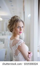 A beautiful woman in a pink wedding dress in a big festive hall