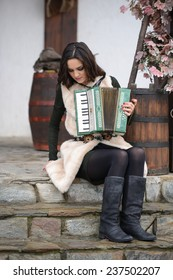 Beautiful woman with playing accordion. Outdoor female fashion portrait