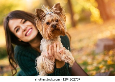 Beautiful woman playing with dog in the park
