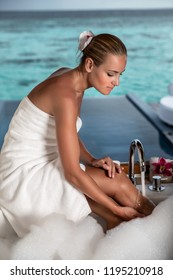 Beautiful woman with pleasure taking bath with foam in the bungalow with open view to the sea, luxury spa resort on Maldives