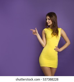 Beautiful woman pointing to the left while smiling. Girl wearing yellow dress on purple background.