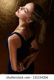 beautiful woman with ponytail wearing stretch dress on gold background with artistic lighting