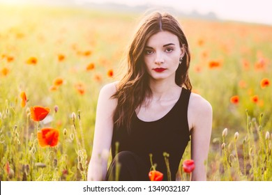 Beautiful woman at poppy field in sunset