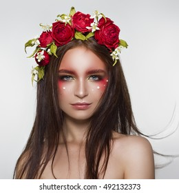 Beautiful woman portrait with bright art makeup and floral crown