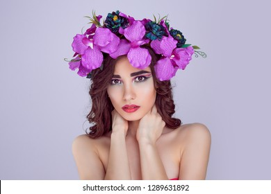 Beautiful woman portrait with bright artistic makeup floral crown flowers magenta pink orchid flowers looks at you camera touching neck perfect skin face dark hair in curls isolated light purple wall