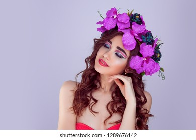 Beautiful woman portrait with bright artistic makeup floral crown flowers magenta pink orchid flowers eyes closed face looking to side touching perfect skin face dark hair in curls isolated on purple
