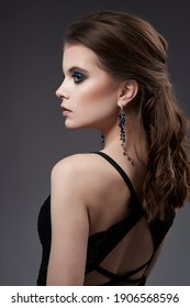 Beautiful woman portrait with earrings and black dress