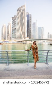 Beautiful woman portrait enjoying the view at Dubai Mall with fountains in the background.