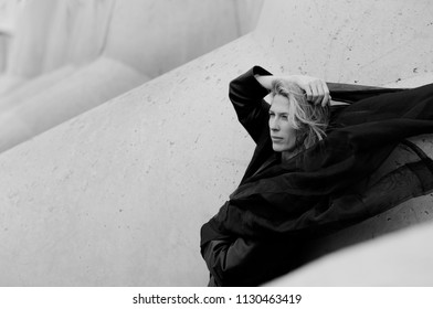 Beautiful woman portrait, flying black scarf and blonde long hair, concrete blocks background in sea port