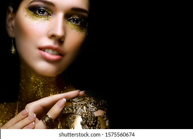 Beautiful woman portrait with golden glitter on her face. Girl with art make-up with golden sparkles. Fashion model with golden makeup