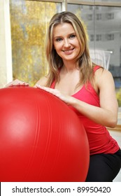 beautiful woman portrait at the gym smiling seating at the pilates ball