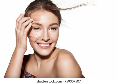 Beautiful woman portrait with hair flies. Female face close up studio portrait, isolated on white. Girl with clean skin and fresh daily make-up. Concept of cosmetology and beauty industry.