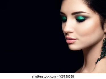 Beautiful woman portrait isolated on black background. Young lady posing with green eye shadows and earrings. Glamour make up. White skin.