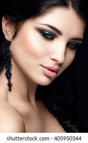 Beautiful woman portrait isolated on black background. Young lady posing with blue eye shadows and earrings. Glamour make up. White skin. Magnetic view.