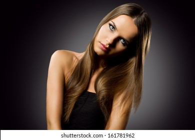 beautiful woman portrait with long healthy hair against black background