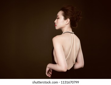 Beautiful woman portrait on black background. Young lady posing with gorgeous make up and hairstyle.