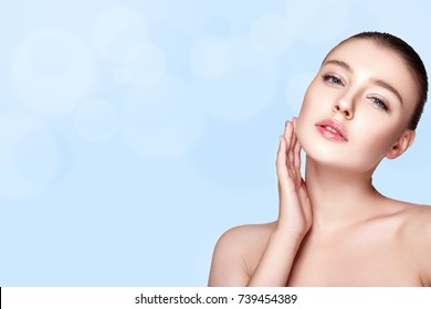 Beautiful woman portrait on blue background with fresh clear nude make up, healthy skin, skin care.