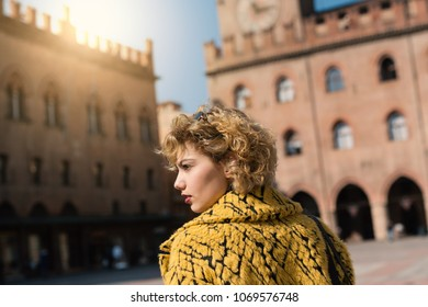 Beautiful woman portrait outdoors in Piazza Maggiore, Bologna, Italy. Natual flare.