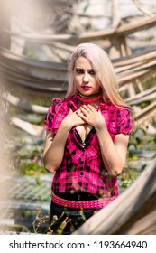 Beautiful woman portrait with punk make up and outfit with bleached hair posing in an abandoned green house where nature has taken its toll