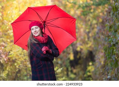 Beautiful woman portrait with red umbrella over yellow autumn background