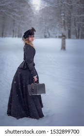 Beautiful woman, portrait in retro style . The girl wearing black vintage dress in the winter's park