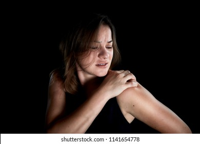 Beautiful woman portrait with shoulder pain. Woman pressing her hand against a painful shoulder, isolated on black background.