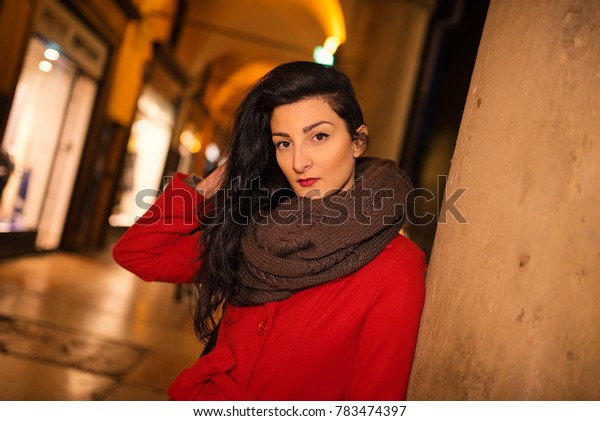 Beautiful woman portrait wearing red coat at night in winter time in the streets of historical city of Bologna, Italy.