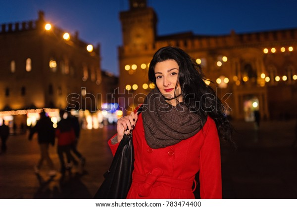 Beautiful woman portrait wearing red coat at twilight in winter time in Maggiore square of the historical city of Bologna, Italy.
