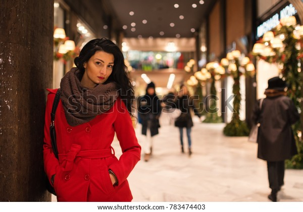 Beautiful woman portrait wearing red coat at night in winter time inside Galleria Cavour. Bologna, Italy.