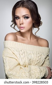 Beautiful woman portrait. Young lady posing in warm sweater. Nice makeup and hairstyle. Studio photo shoot.