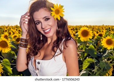 Beautiful woman poses in the agricultural field with sunflower on a sunny summer day