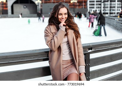 Beautiful woman posing alone and smiling in winter in the park near the ice rink