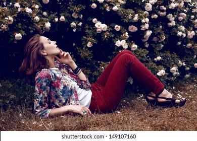 Beautiful woman posing behind rose bush. Botanical garden, outdoor fashion shot