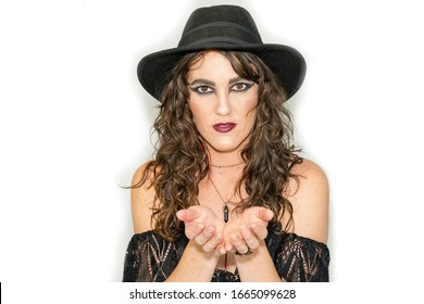Beautiful woman posing in black lace dress and wide brim hat isolated on white background