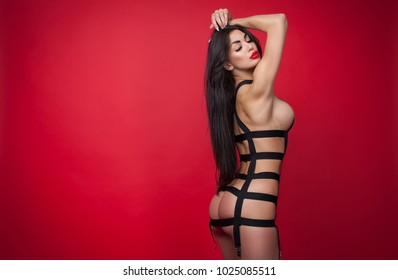 Beautiful Woman Posing In black Lingerie Isolated On Red Background