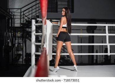 Beautiful woman posing in boxing ring. Young sporty woman standing on ring and resting