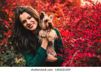 Beautiful woman posing with dog on red tree leaf background.