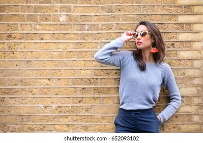 Beautiful woman posing in front of a brick wall