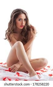 Beautiful woman posing naked with rose petals