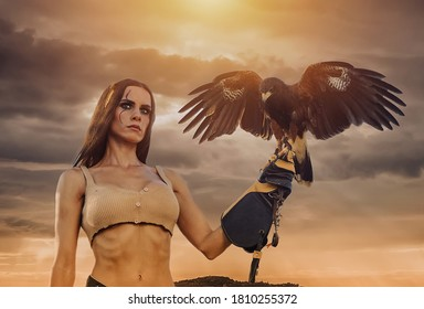 Beautiful woman posing on nature with eagle against cloudy sky during sunset