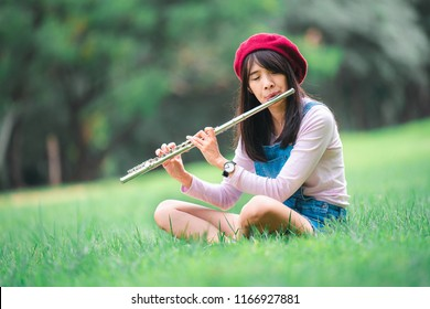 A beautiful woman posing in a park while playing on a flute.